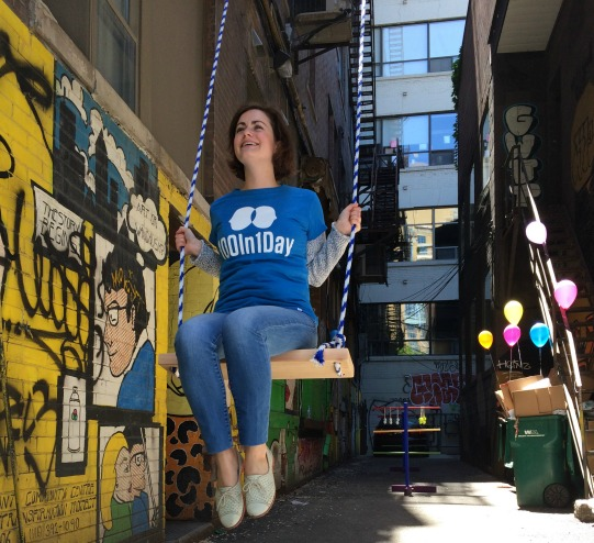 A girl on a swing in a laneway.
