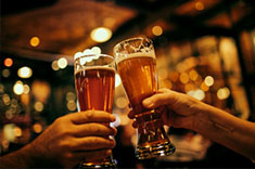 Two people clinking their beer glasses together.