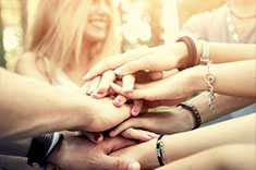 A group of people piling their hands together.