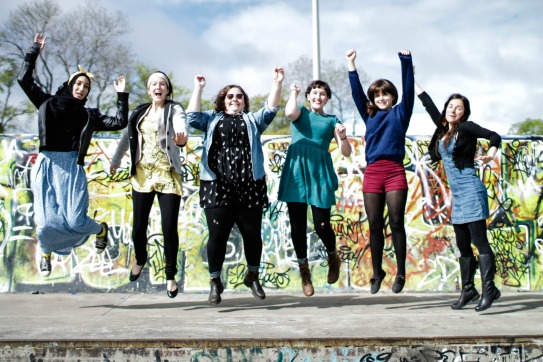 Young adults jumping and smiling in front of urban landscape.
