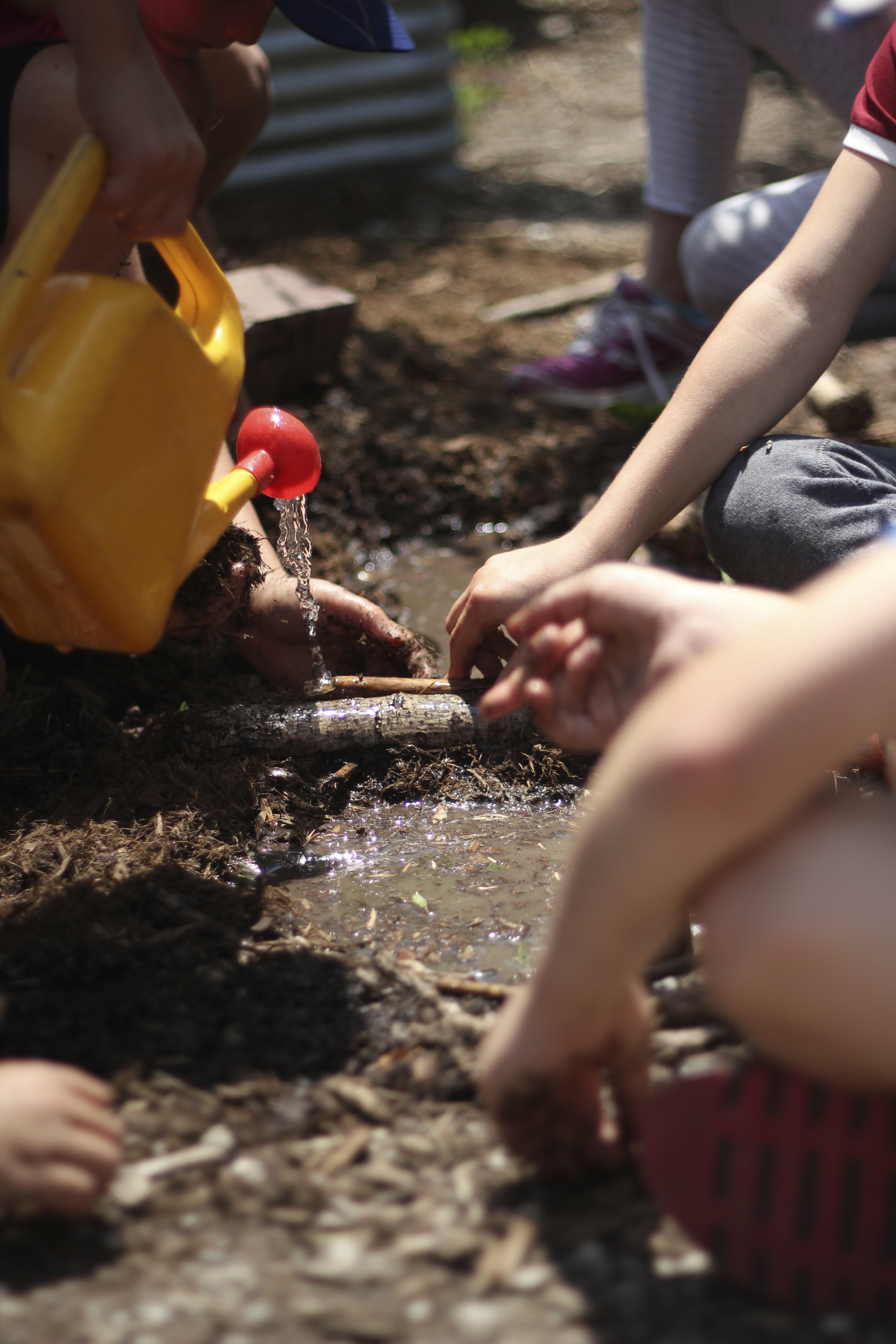 Children play with watering cans and buckets.