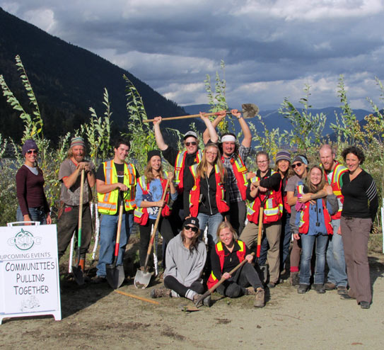 A group of people with shovels and reflector vests gather after planting trees with mountains in the background. Photo: Central Kootenay Invasive Plant Committee.