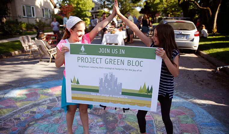 Two girls high-fiving while holding a Project Green Bloc sign. (Photo: Mychaylo Prystupa)