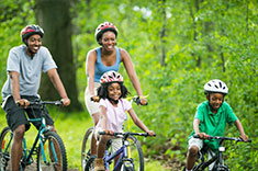 A family biking in a forest.