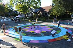 Community members painting a mural on their street. (Photo: Ellen Li)