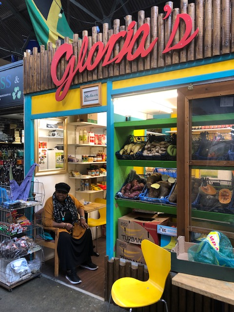 A vendor at the Tooting Market sits outside her stall.