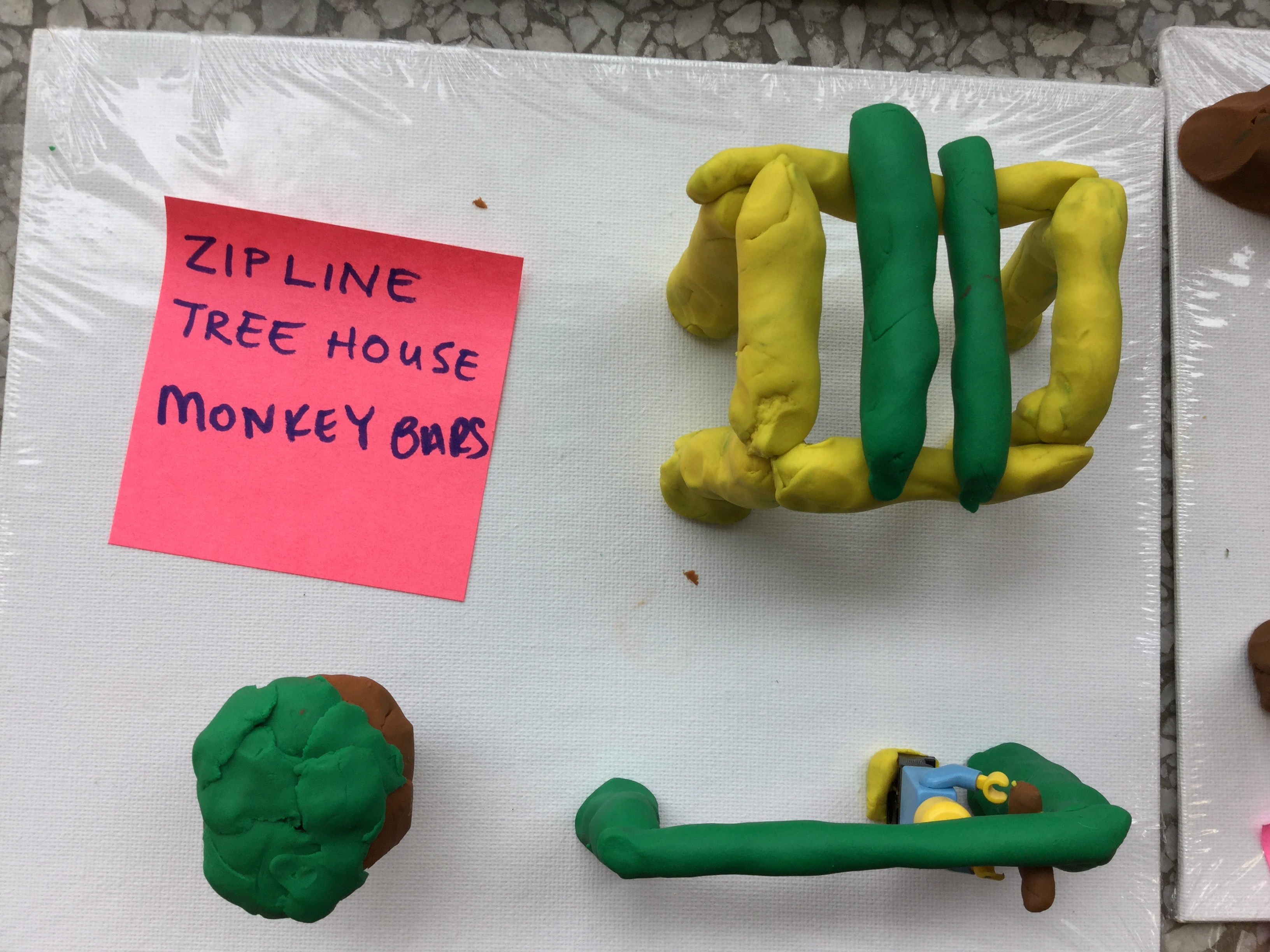 One of the clay sculptures students made that shows a zip line and a tree house.