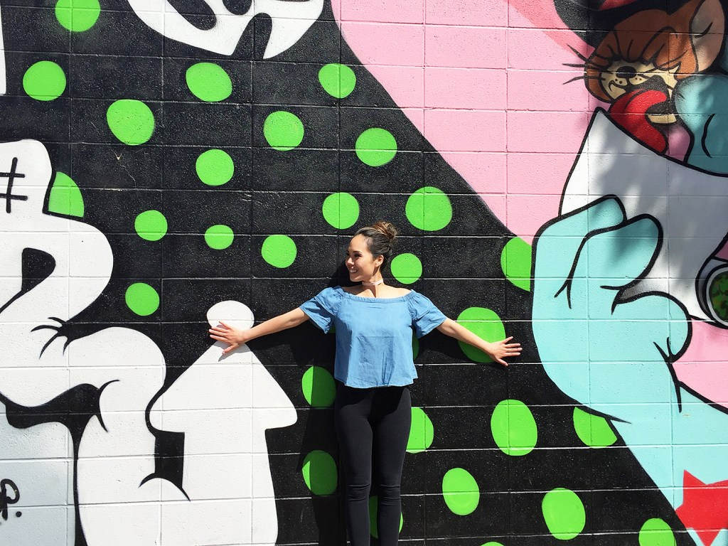 A woman poses in front of a graffiti wall in downtown Edmonton.