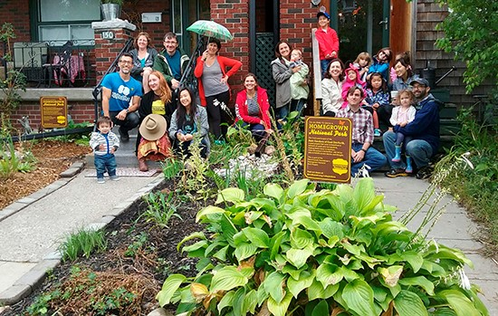 Residents pose in a rain garden for 100In1Day Toronto.