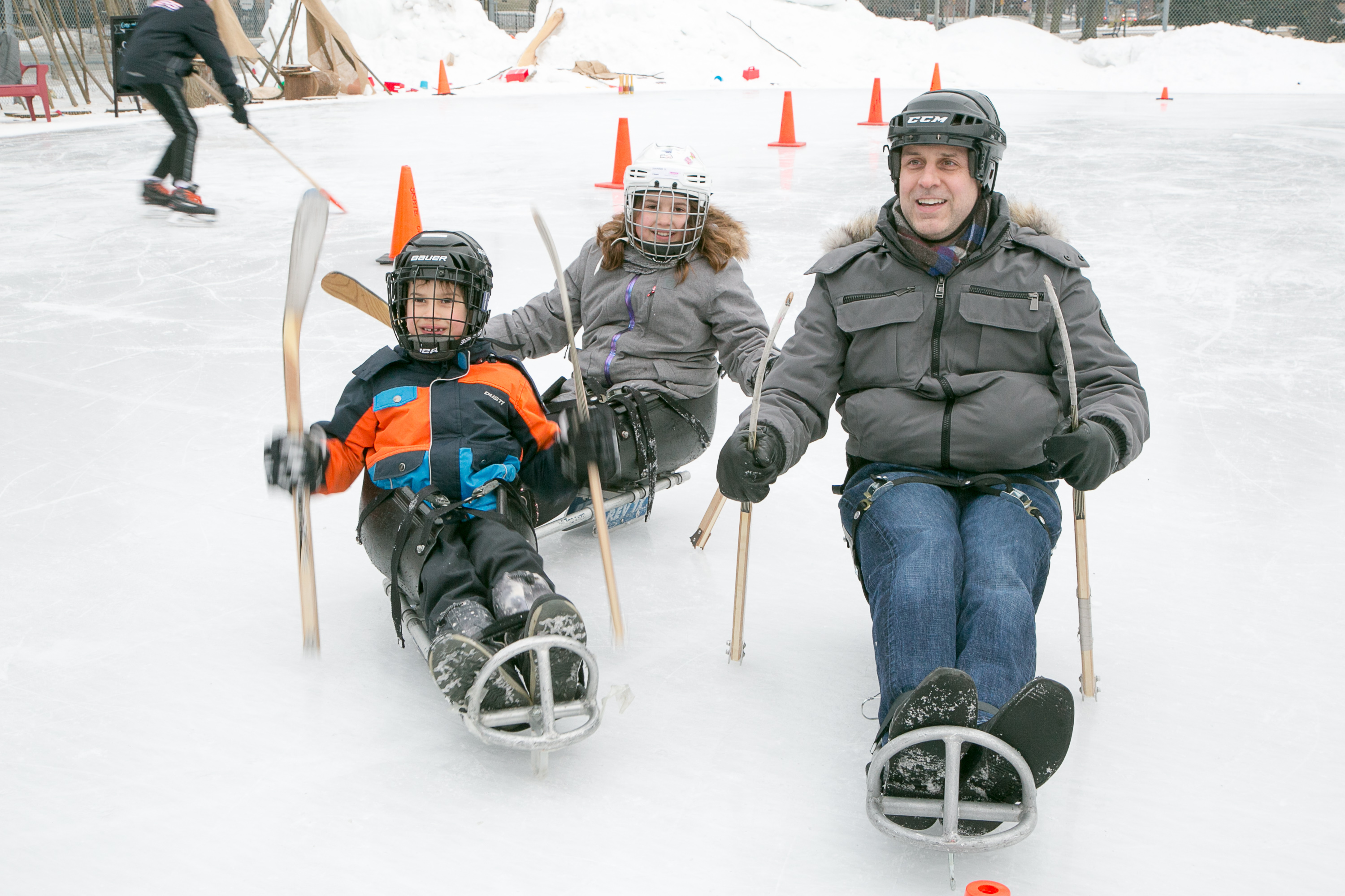Families sledge on the ice at Rink Social.