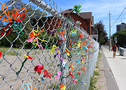 A chain-link fence decorated with colorful pipe cleaners.