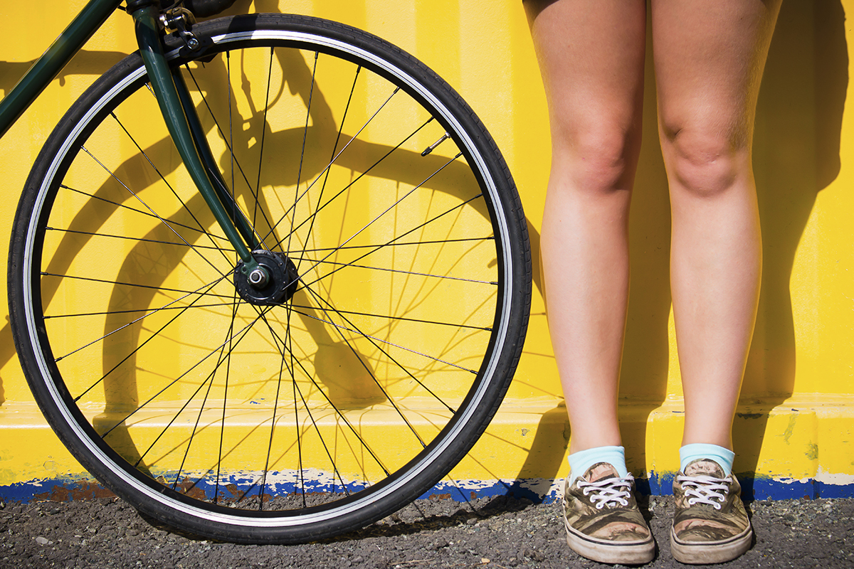 Bicycle wheel beside rider's legs