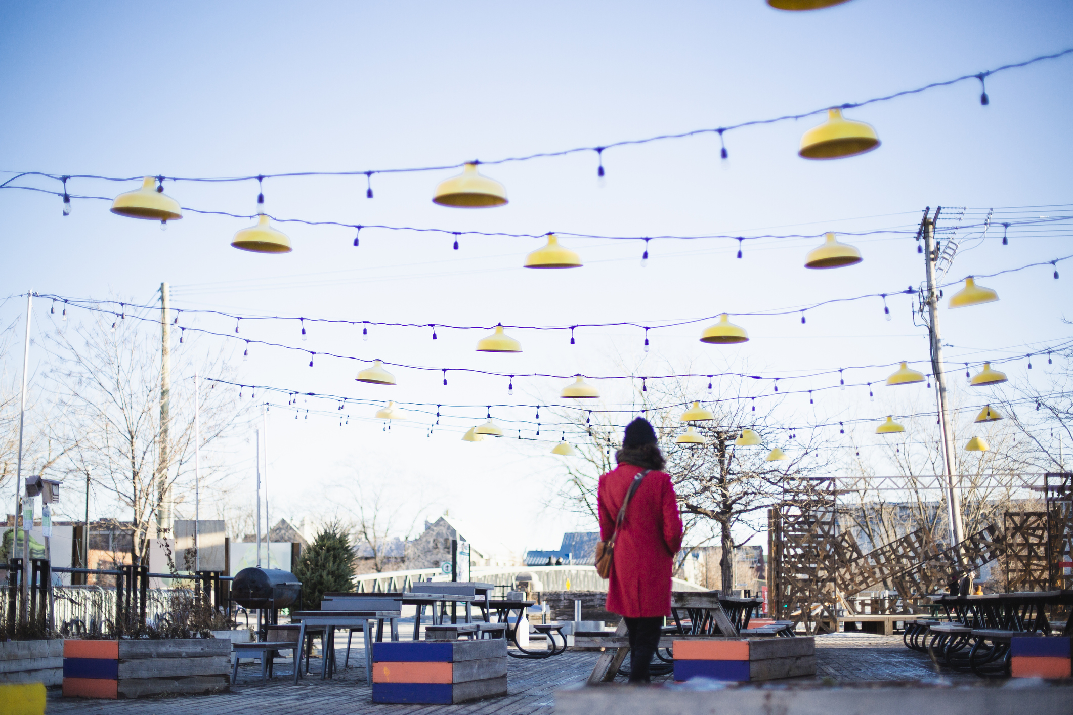 A person in a red coat stands in front of empty picnic tables and string lights