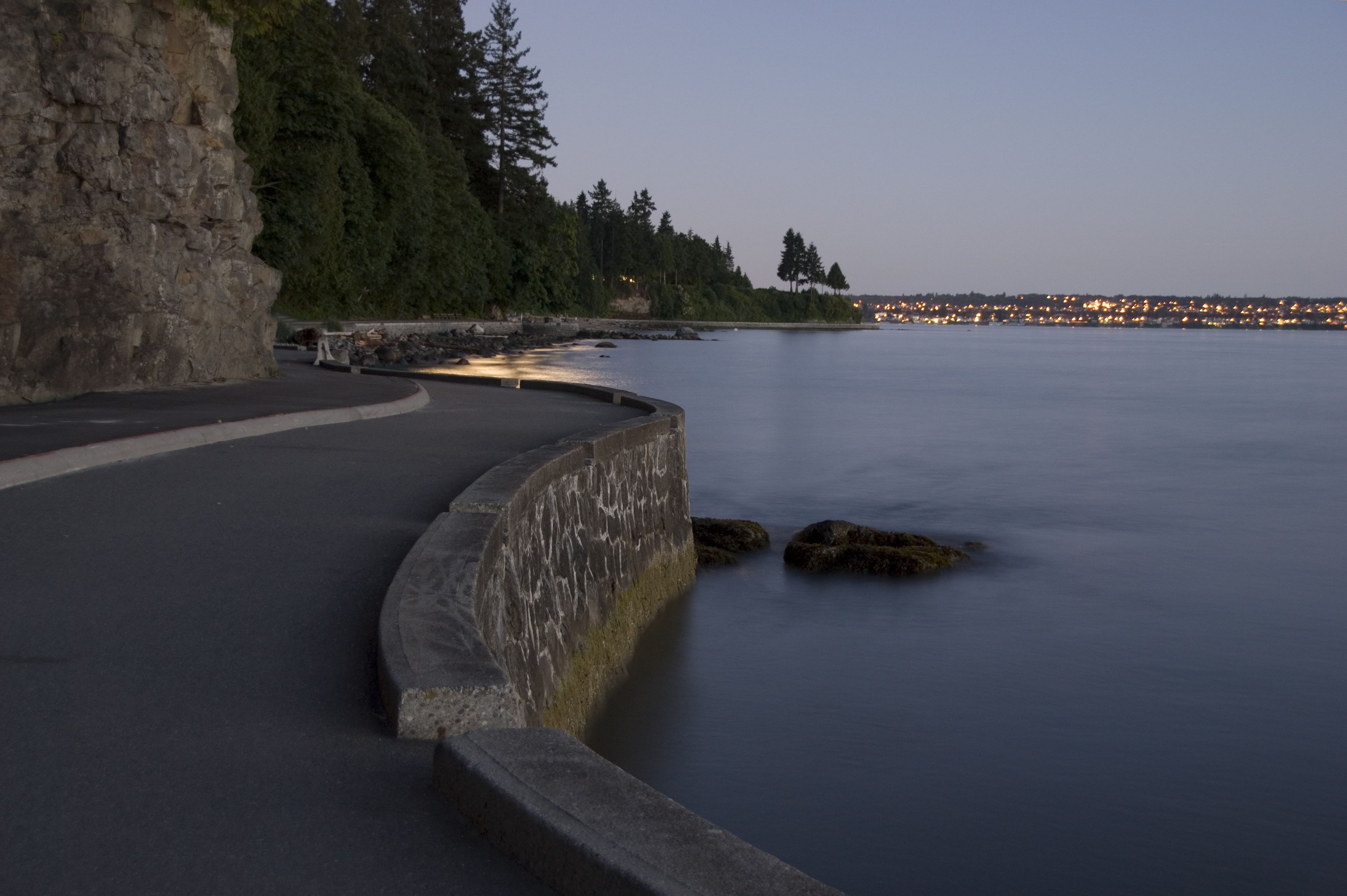 A stretch of paved road running along the waterfront, with Vancouver in the background