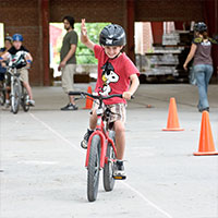 A young boy practicing riding a bike at an Evergreen Brick Works camp program. Image Credit: Jan Schwarz