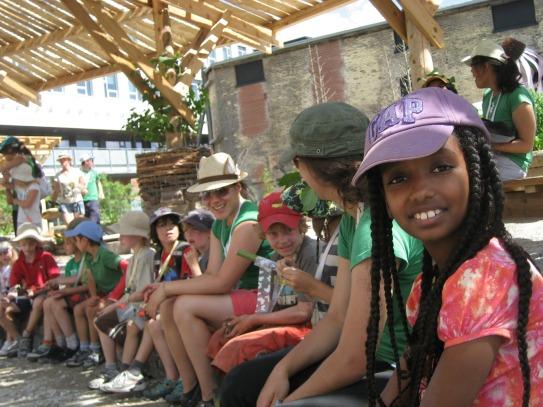 Children sitting on a bench in the Children's Garden.