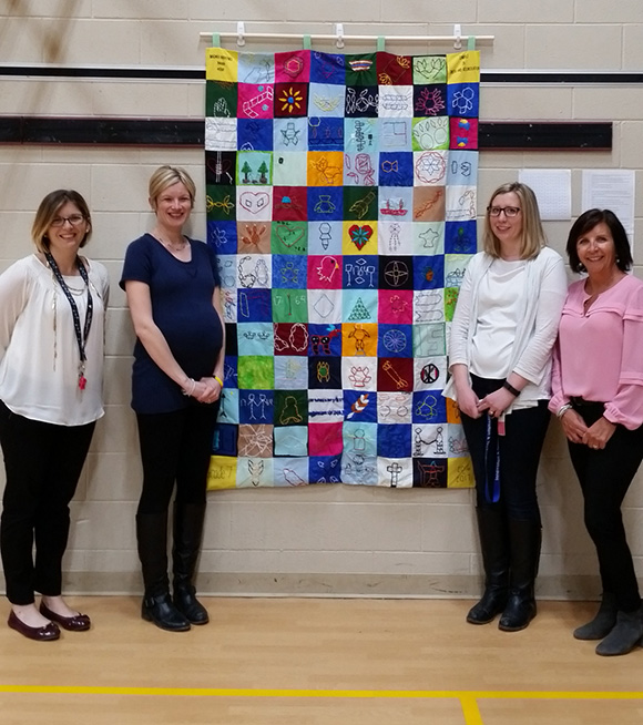 Teachers- Sarah Patterson, Christine Vanderwal, Shannon Jacobs, Shari Keast with a quilt designed by Grade 7 students to represent different aspects of indigenous culture.