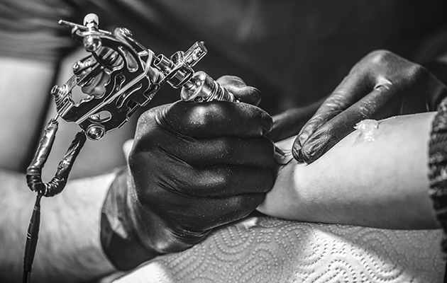A tattoo artist giving someone a tattoo on their arm.