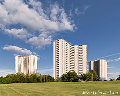 High-rise apartment buildings behind a green field. Photo: Jesse Colin Jackson