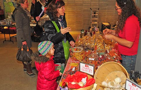 A mother and daughter speak to one of the farmer vendors at the EBW Winter Farmers' Market. Photo: Lyle Sadavoy.