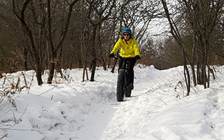 A person riding a fat tire bike in the snow.