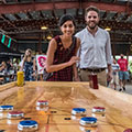 A young couple playing shuffleboard in the Pavilions at Evergreen Brick Works.