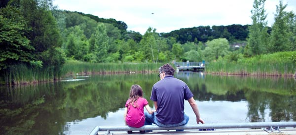 A father and daughter take a moment to relax in front of the ponds. Photo: Geoff Fitzgerald.