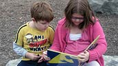 Two young students sit in their outdoor classroom and read a book. Photo: Evergreen.