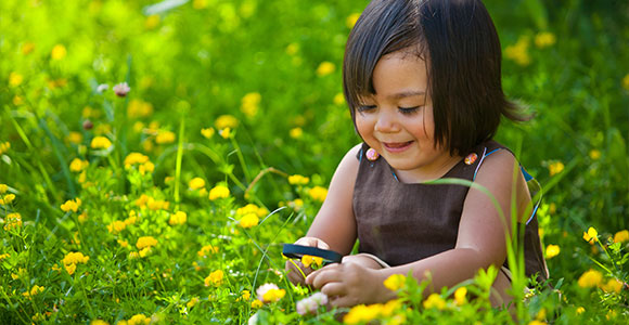 A young girl looking at a plant with a magnifying glass.